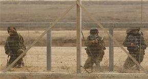 Um soldado israelense aponta sua arma para palestinos que chegaram à fronteira entre Israel e o sul da Faixa de Gaza. 23/11/2012 REUTERS/Ibraheem Abu Mustafa