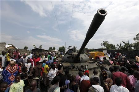 People gather around a tank abandoned by fleeing Congolese army in Ndosho near Goma November 21, 2012. Foreign ministers from nine African countries on Wednesday urged other nations on the continent to contribute troops to an international force to fight rebels in the Democratic Republic of Congo's turbulent east, a Ugandan government spokesman said. The plea - which comes at a time when the M23 rebels appear to have the Congolese army on the backfoot - was signed by Congo, Rwanda, Uganda, Burundi, Tanzania, Kenya, Sudan, Congo Republic and Zambia. REUTERS-James Akena