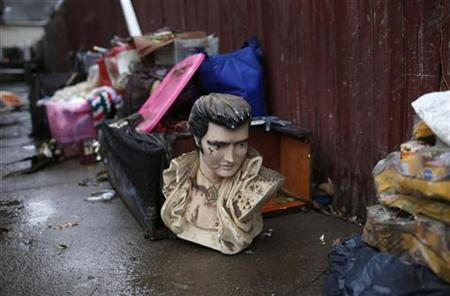 A bust of Elvis Presley lays out with debris on a sidewalk next to a destroyed home after flooding from Hurricane Sandy in the Midland Beach neighborhood of Staten Island in New York City, November 13, 2012. REUTERS/Mike Segar