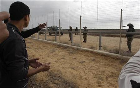 A Palestinian looks at Israeli soldiers as they stand guard behind the fence between Israel and southern Gaza Strip November 23, 2012. REUTERS/Ibraheem Abu Mustafa