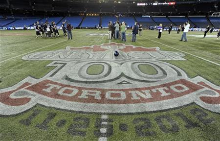 Toronto Argonauts players are interviewed on the field behind the Grey Cup logo during practice ahead of the 100th Grey Cup CFL football game in Toronto November 23, 2012. The Grey Cup CFL championship football game between the Argonauts and the Calgary Stampeders will be played on November 25. REUTERS/Mike Cassese