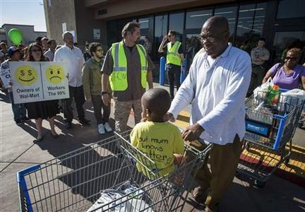 Walmart customers leave the store as they are greeted by striking Walmart workers and supporters during a protest on Black Friday in Paramount, California, November 23, 2012.REUTERS/Bret Hartman