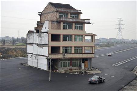 11月22日、中国浙江省温嶺市で、新たに整備された道路の真ん中に住宅が1軒だけ残されている。老夫婦が立ち退きを拒否したため、住宅がそのまま残されたという(2012年 ロイター/China Daily)