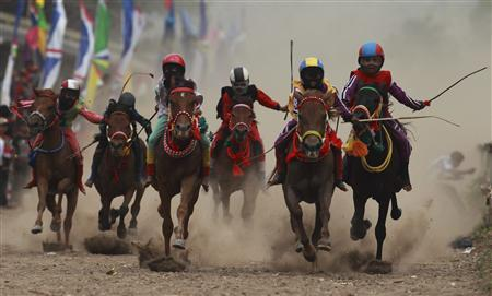 Child jockeys race their horses at a racetrack outside Bima, November 17, 2012. REUTERS/Beawiharta