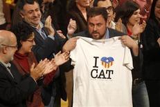 """Los hacendosos catalanes creen que sus firmas de talla mundial y su economía volcada en la exportación - casi del tamaño de la de Portugal - irían mejor sin el resto de España. En la imagen, el candidato presidencial al gobierno catalán de Esquerra Republicana (ERC), Oriol Junqueras, muestra una camiseta con el logo """"Amo Catauña"""" en el acto de cierre de campaña electoral, en Gerona, el 23 de noviembre de 2012. REUTERS/Gustau Nacarino"""