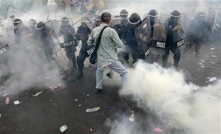 Tear gas is thrown as police scuffle with anti-government protesters in Bangkok November 24, 2012. REUTERS/Sukree Sukplang