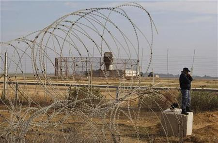 A member of the Hamas security forces stands guard as an Israeli watchtower (rear) is seen near the fence between Israel and the southern Gaza Strip November 24, 2012. REUTERS/ Ibraheem Abu Mustafa