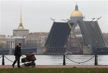 A man pushes a pram along an embankment close to the Palace Bridge, unusually open to allow repair work, in St. Petersburg, November 24, 2012. REUTERS/Alexander Demianchuk