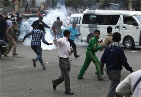 Anti-Mursi protesters run from tear gas released by police during clashes in front of the Supreme Judicial Council in Cairo November 24, 2012. REUTERS/Asmaa Waguih