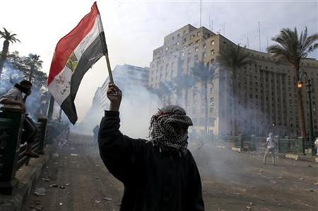 A protester waves an Egyptian flag amidst clashes in Tahrir, Cairo November 25, 2012. Egyptian President Mohamed Mursi's decree that put his decisions above legal challenge until a new parliament was elected caused fury amongst his opponents on Friday who accused him of being the new Hosni Mubarak and hijacking the revolution. Police fired tear gas in a street leading to Cairo's Tahrir Square, heart of the 2011 anti-Mubarak uprising, where thousands demanded Mursi quit and accused him of launching a ''coup''. There were violent protests in Alexandria, Port Said and Suez. REUTERS/Mohamed Abd El Ghany (EGYPT - Tags: CIVIL UNREST POLITICS)