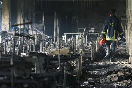 A firefighter inspects a garment factory after a fire in Savar November 25, 2012. A fire swept through Tazreen Fashion factory in the Ashulia industrial belt of Dhaka, on the outskirts of Bangladesh's capital killing more than 100 people, the fire brigade said on Sunday, in the country's worst ever factory blaze. REUTERS/Andrew Biraj (BANGLADESH - Tags: DISASTER BUSINESS EMPLOYMENT)