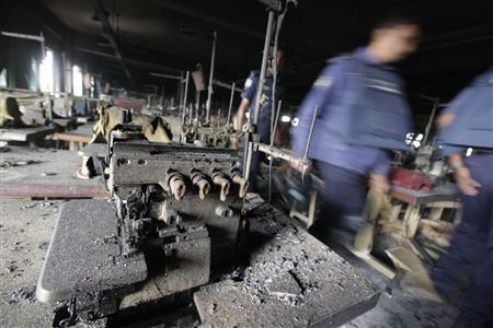 Members of the police inspect the burnt interior of a garment factory after a fire in Savar November 25, 2012.  REUTERS/Andrew Biraj