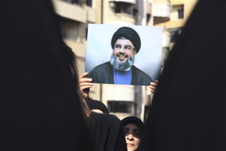 A Lebanese Hezbollah supporter carries a picture of Hezbollah leader Sayyed Hassan Nasrallah as she takes part in a ceremony marking Ashura in Beirut's suburbs, November 25, 2012. Hezbollah leader Sayyed Hassan Nasrallah warned Israel on Sunday that thousands of rockets would rain down on Tel Aviv and other Israeli cities if Israel attacked Lebanon. REUTERS/Khalil Hassan