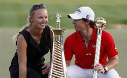 Rory McIlroy of Northern Ireland smiles at his girlfriend tennis player Caroline Wozniacki of Denmark as he poses with his trophy after the fourth and final round of the DP World Tour Championship at Jumeirah Golf Estates in Dubai November 25, 2012. REUTERS/Nikhil Monteiro