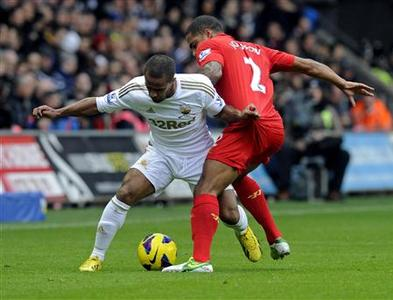 Swansea's Wayne Routledge (L) challenges Liverpool's Glen Johnson during their English Premier League soccer match at the Liberty Stadium in Swansea, South Wales November 25, 2012. REUTERS/Rebecca Naden