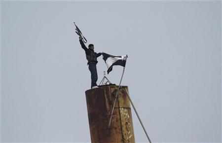 A member of the Free Syrian Army fires his weapon after lowering a Syrian flag and raising a Syrian opposition flag, as gunfire is heard between them and the armed Kurds of The Kurdish Democratic Union Party (PYD) in the northern Syrian town of Ras al-Ain, November 25, 2012. REUTERS/Amr Abdallah Dalsh