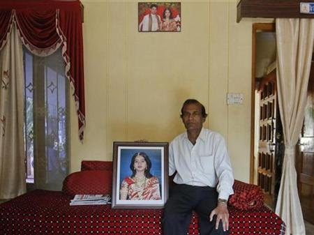 Andanappa Yalagi, father of Savita Halappanavar holds her portrait as he poses for a picture at their house in Belgaum in Karnataka November 16, 2012. REUTERS/Danish Siddiqui