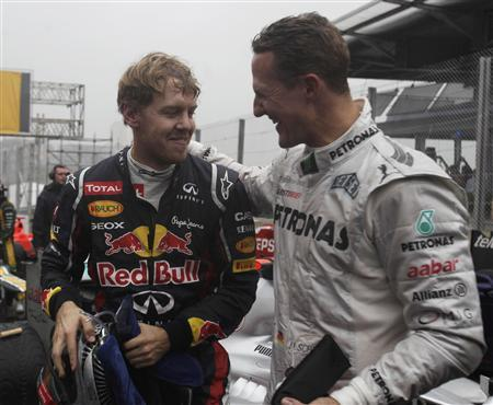 Mercedes Formula One driver Michael Schumacher of Germany (R) congratulates compatriot Red Bull driver Sebastian Vettel after the Brazilian F1 Grand Prix at Interlagos circuit in Sao Paulo November 25, 2012. Vettel became Formula One's youngest triple world champion at the age of 25 at the Brazilian Grand Prix on Sunday. REUTERS/Ricardo Moraes