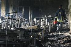 Bombeiro inspeciona uma fábrica de roupas após o incêndio em Savar. O fogo se alastrou por uma fábrica de roupas nos arredores da capital de Bangladesh, matando mais de 100 pessoas, informou o Corpo de Bombeiros no domingo, no pior incêndio já registrado em uma fábrica do país. 25/11/2012 REUTERS/Andrew Biraj
