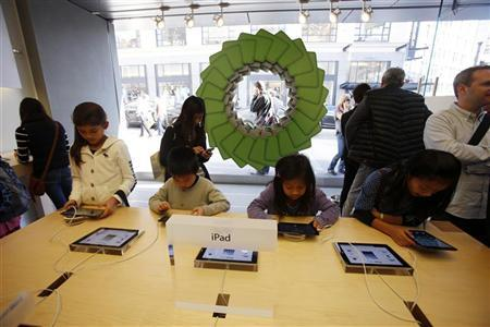 Young holiday shoppers interact with the iPad at the Apple Store during Black Friday in San Francisco, California, November 23, 2012. REUTERS/Stephen Lam