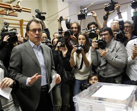 Convergencia i Unio (CIU) party's candidate Artur Mas is surrounded by photographers before casting his vote for the Catalunya's regional government at Barcelona November 25, 2012. REUTERS/Gustau Nacarino
