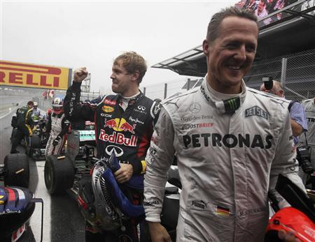 Red Bull Formula One driver Sebastian Vettel of Germany (L) celebrates winning the world championship next to compatriot Mercedes driver Michael Schumacher after the Brazilian F1 Grand Prix at Interlagos circuit in Sao Paulo November 25, 2012. Vettel became Formula One's youngest triple world champion at the age of 25 at the Brazilian Grand Prix on Sunday. REUTERS/Ricardo Moraes
