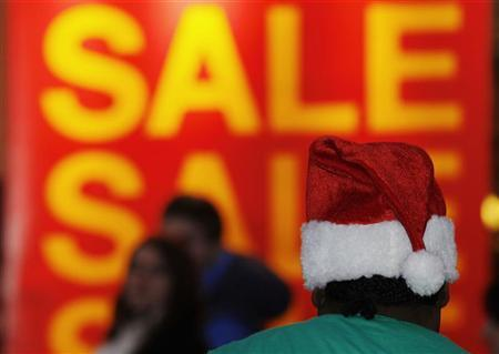 Shoppers walk pass sale signs and a busker along Oxford Street on the penultimate Saturday before Christmas in London December 17, 2011. REUTERS/Luke MacGregor
