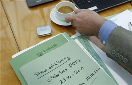 A man reaches for a cup of coffee in Frankfurt October 29, 2012. REUTERS/Lisi Niesner/Files