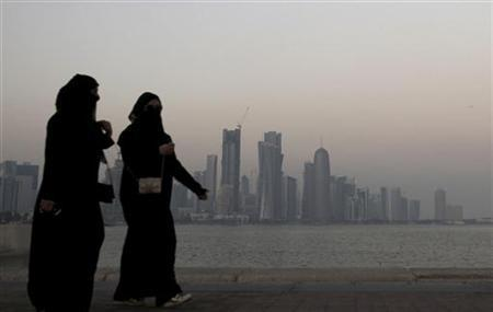 Women walk past buildings as the sun sets in Doha October 19, 2010. REUTERS/Fadi Al-Assaad/Files