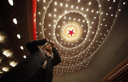 A staff member takes a photo inside the Great Hall of the People where the 18th National Congress of the Communist Party of China is taking place, in Beijing November 14, 2012. REUTERS/Carlos Barria
