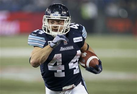 Toronto Argonauts Chad Kackert runs for extra yardage against the Calgary Stampeders in the second half during the 100th CFL Grey Cup championship football game in Toronto, November 25, 2012. REUTERS/Christinne Muschi