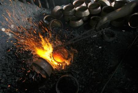 A labourer works inside a copper workshop in Siliguri June 6, 2009. REUTERS/Rupak De Chowdhuri/Files