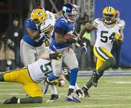 New York Giants running back Andre Brown (35) breaks past Green Bay Packers inside linebacker A.J. Hawk (bottom L) and linebacker Dezman Moses (54) for a long gain in the second quarter of their NFL football game in East Rutherford, New Jersey November 25, 2012. REUTERS/Ray Stubblebine
