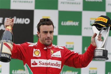 Second placed Ferrari Formula One driver Fernando Alonso of Spain celebrates on the podium after the Brazilian F1 Grand Prix at Interlagos circuit in Sao Paulo November 25, 2012. REUTERS/Paulo Whitaker