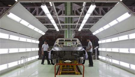 Workers inspect the body of a Mahindra & Mahindra's XUV 500 vehicle on the assembly line at the company's vehicle manufacturing plant in Chakan, outside Pune, September 29, 2011. REUTERS/Vivek Prakash/Files