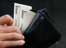 El euro subía a su nivel más alto en siete meses frente al yen y se mantenía cerca de su máximo de un mes contra el dólar en la sesión cambiaria en Asia, alentado por las esperanzas de que el eurogrupo apruebe el lunes una solución al menos temporal para Grecia. En la imagen, un hombre sostiene billetes de 10.000 yenes frente a un banco en Tokio, el 22 de noviembre de 2012. REUTERS/Kim Kyung-Hoon