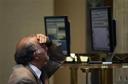 A trader looks at computer screens at Madrid's bourse August 2, 2012. REUTERS/Susana Vera/Files