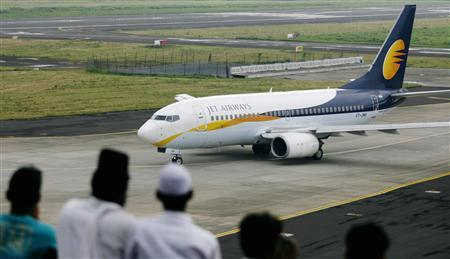People look at a Jet Airways aircraft preparing to take off from the airport in Mumbai in this September 13, 2009 file photo. Loss-making carriers Jet Airways and SpiceJet are in talks with Abu Dhabi's Etihad Airways and Malaysia's AirAsia Bhd, respectively, to sell minority stakes, a government source said. Any deal would be the first since India changed its rules in September 2012 to allow foreign carriers to buy stakes of up to 49 percent in local airlines, which have been battered by fierce competition and high operating costs. REUTERS/Punit Paranjpe/Files