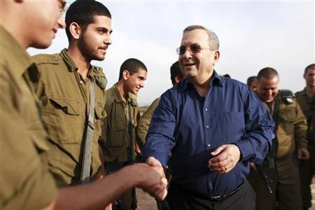 Israel's Defence Minister Ehud Barak (C) shakes hands with a soldier during a news conference at the site where an Iron Dome anti-missile battery has been deployed near Tel Aviv November 18, 2012. REUTERS/Daniel Bar-On