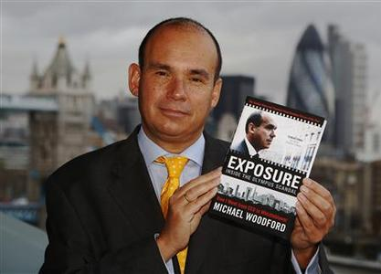 Former CEO at Olympus Corporation Michael Woodford poses with his book ''Exposure'' in London November 22, 2012. REUTERS/Luke MacGregor