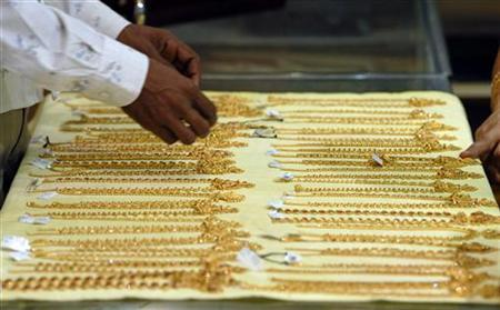 A salesman displays gold chains at a jewellery showroom in Hyderabad April 27, 2009. REUTERS/Krishnendu Halder/Files