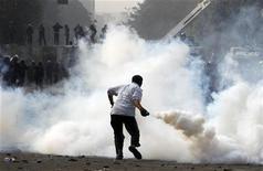 Manifestante atira bomba de gás contra policiais no Cairo em meio a protestos na capital egípcia após o presidente do país decretar que suas decisões estão acima da lei até a eleição do parlamento. 25/11/2012 REUTERS/Mohamed Abd El Ghany