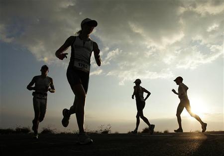 Amateur competitors run along Queen Kaahumanu Highway during the marathon section of the Ironman World Championship triathlon in Kailua-Kona, Hawaii October 13, 2012. REUTERS/Hugh Gentry