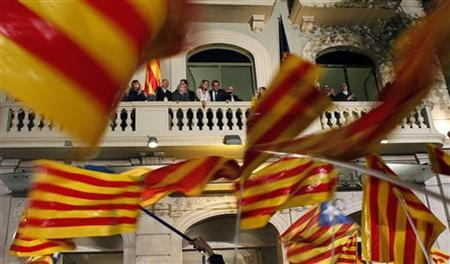 Convergencia i Unio (CIU) party candidate for Catalunya's regional government Artur Mas and his wife Helena Rakosnik look at supporters from a balcony in Barcelona November 25, 2012. Four separatist parties in Spain's Catalonia looked set to win a majority in regional elections on Sunday, partial results showed, but the main one was on course to lose some seats, possibly undermining its bid to call an independence referendum. REUTERS/Albert Gea (SPAIN - Tags: POLITICS ELECTIONS)