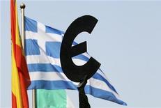 Bandeira grega tremula ao fundo de uma estátua com o símbolo do euro do lado de fora do Parlamento Europeu, em Bruxelas. O Fundo Monetário Internacional (FMI) e ministros das Finanças da zona do euro tentarão descongelar o segundo pacote de resgate para a Grécia . 22/05/2012 REUTERS/Francois Lenoir