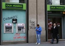 Pessoas diante de agência do banco espanhol Bankia com pichações na parede, no centro de Madri. O governo espanhol vai pedir entre 40 bilhões e 42,5 bilhões de euros (52 bilhões a 55 bilhões de euros) em ajuda financeira para seus bancos em crise. 15/11/2012 REUTERS/Andrea Comas