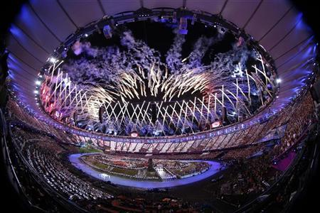 The Olympic flag is carried as fireworks explode during the opening ceremony of the London 2012 Olympic Games at the Olympic Stadium July 27, 2012. REUTERS/Jorge Silva