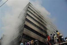 Bombeiros tentam controlar incêndio em fábrica têxtil na periferia de Dhaka, Bangladesh. Milhares de trabalhadores enfurecidos do setor têxtil participaram de manifestações na periferia de Dhaka, nesta segunda-feira, após um incêndio que destruiu uma fábrica de roupas no fim de semana, matando mais de 100 pessoas, no pior incidente do tipo em um indústria na história de Bangladesh. 26/11/2012 REUTERS/Stringer
