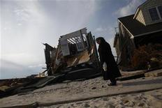 A woman stands near her home that was destroyed by Hurricane Sandy in Ortley Beach, New Jersey November 25, 2012. REUTERS/Eric Thayer (UNITED STATES - Tags: DISASTER SOCIETY)
