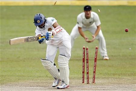 Sri Lanka's Tillakaratne Dilshan (L) is bowled out by New Zealand's Tim Southee during the second day of their second and final test cricket match in Colombo, November 26, 2012. REUTERS/Dinuka Liyanawatte